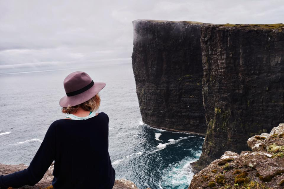 A woman looks out over the dramatic sea cliffs of the Faroe Islands.