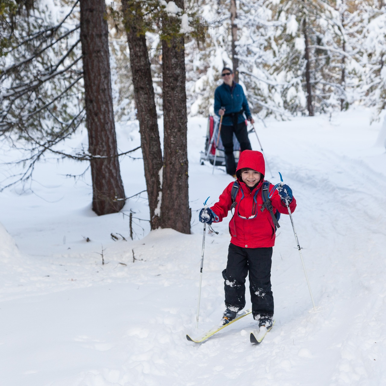 Smiling kid and mother cross-country skiing.