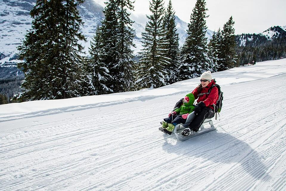 Mother and child riding a toboggan in Switzerland. Photo: Jesse Cunningham