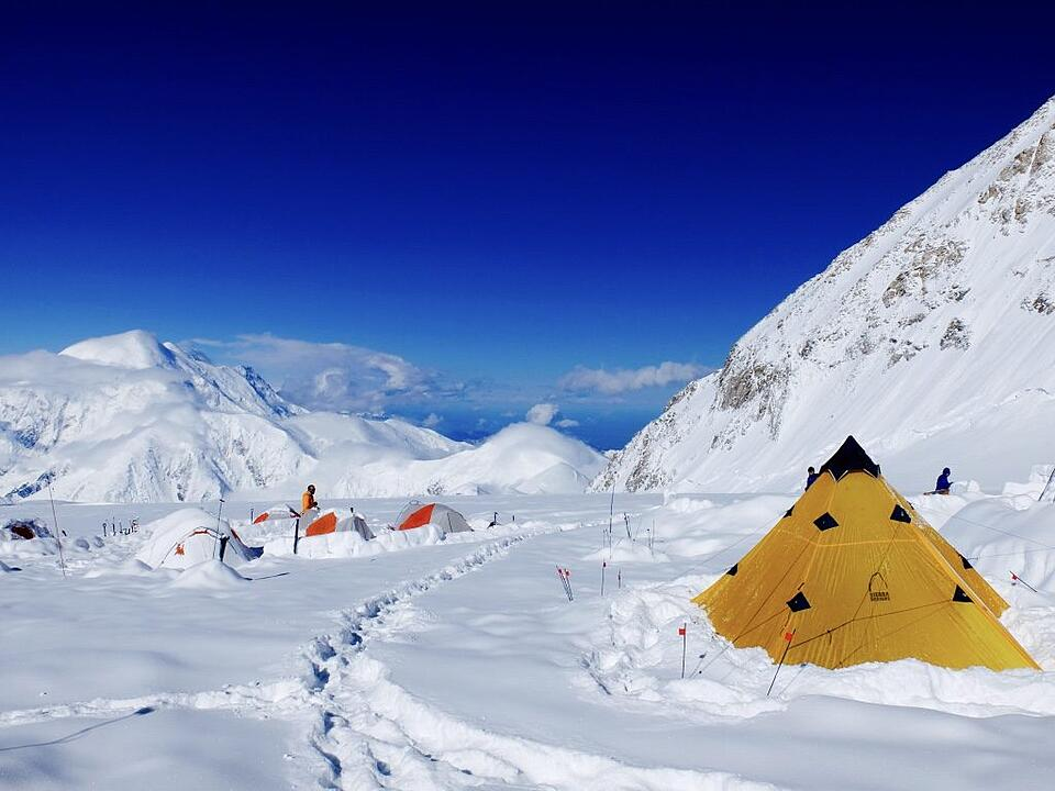Tents buried in snow around Denali on a sunny day.